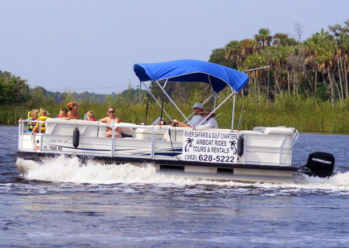 River Safaris tour pontoon boat with several young children at the bow